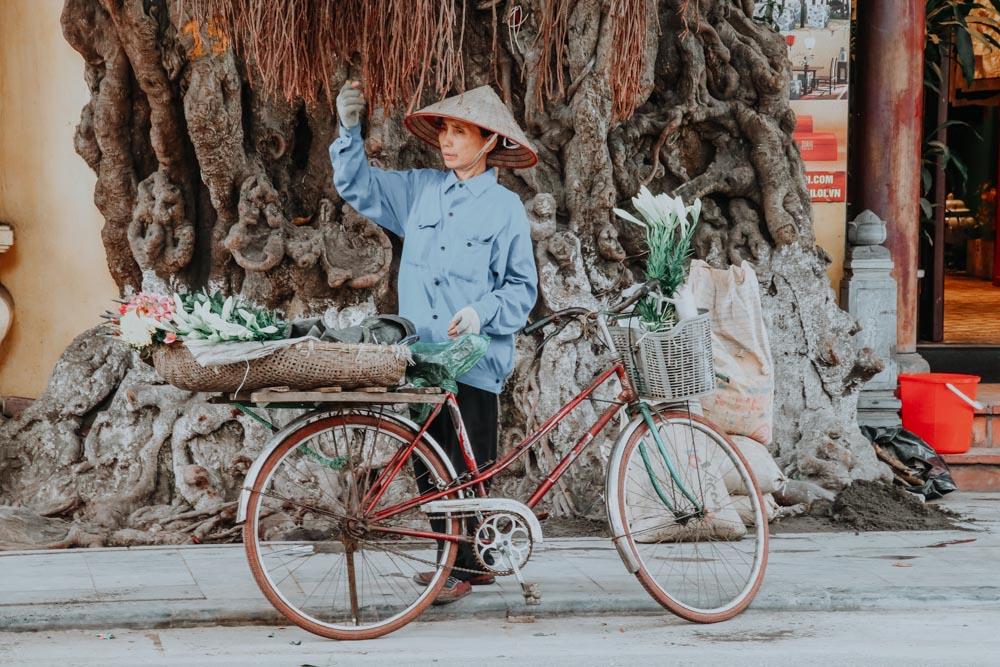 Eine Blumenverkäuferin in der Altstadt von Hanoi