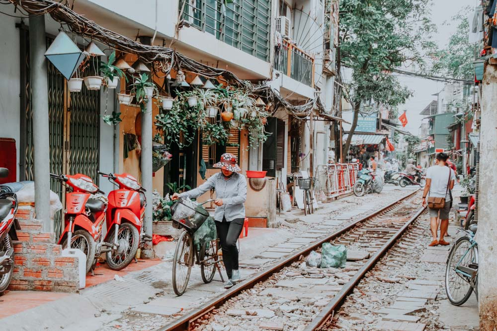 Frau schiebt ihr Fahrrad durch die Hanoi Train Street