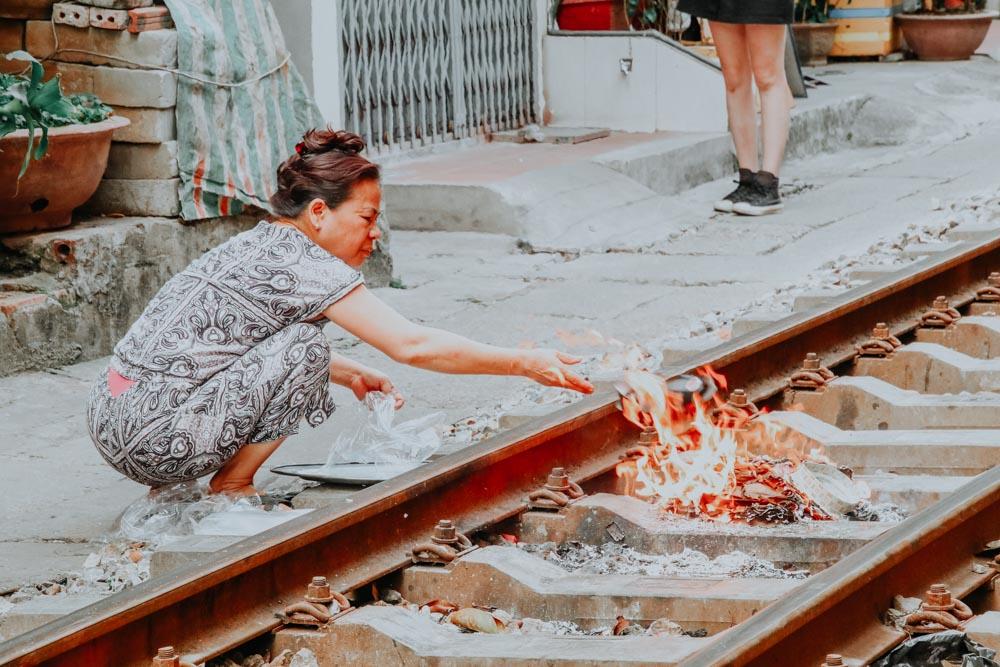 Frau verbrennt Joss Papers auf den Bahngleisen der Train Street