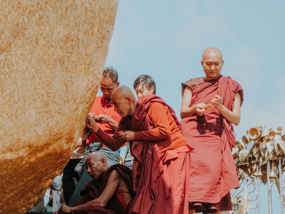 Mönche kleben Blattgold auf den Goldenen Felsen